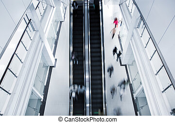 Motion blurred people on stairs and escalator