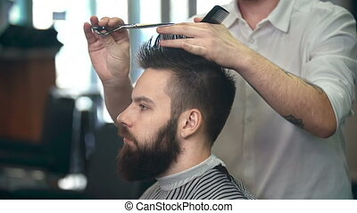 At the Barbershop - Side view of man having his hair cut by...