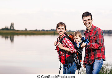 Happy family outdoors. Baby boy in backpack carrier on...