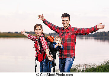 Happy family outdoors with hands outstretched. Baby boy in...