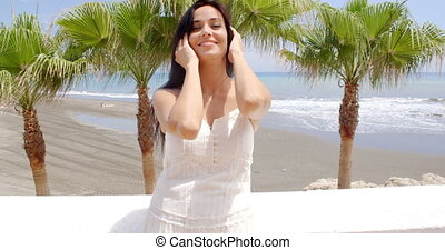 Woman in White Dress Leaning Against Beach Wall - Waist Up...