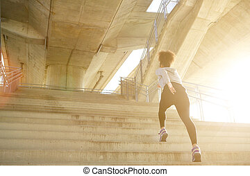 Progression - Young exercise woman running alone up stairs