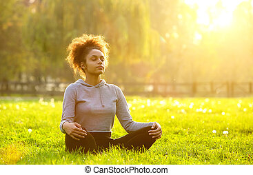 African american woman meditating in nature - Young african...