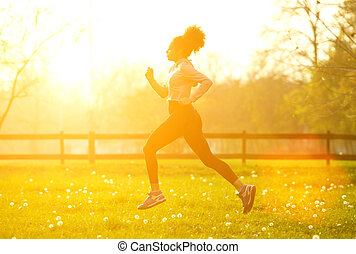 Exercise woman running outdoors - Side view full body...
