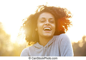 Happy young woman laughing outdoors - Close up portrait of a...