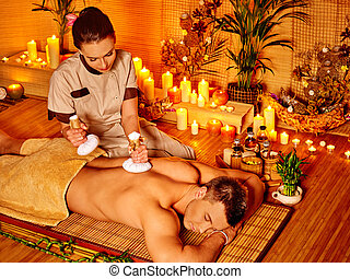 Man getting herbal ball massage treatments . - Man getting...