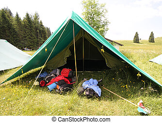 big tent of boy scout camp with backpacks and sleeping bags...