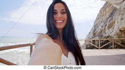 Brunette Woman Taking Self Portrait by Ocean - Attractive...