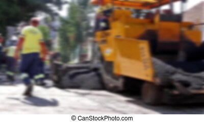 Road Construction in blurred view - Hot asphalt is applied...