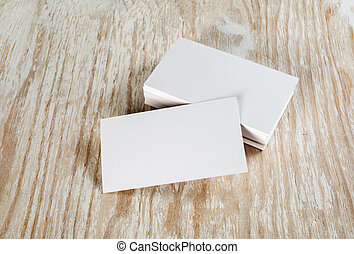 Blank business cards with soft shadows on light wooden...