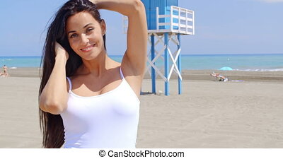Brunette Woman on Beach Shading Eyes with Hand - Attractive...