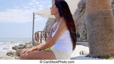 Brunette Woman Sitting on Stone Wall by Ocean
