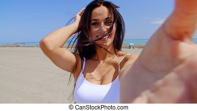 Smiling Woman Taking Self Portrait on Windy Beach - Smiling...