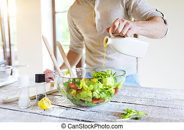 Man with salad - Unrecognizable man in the kitchen preparing...
