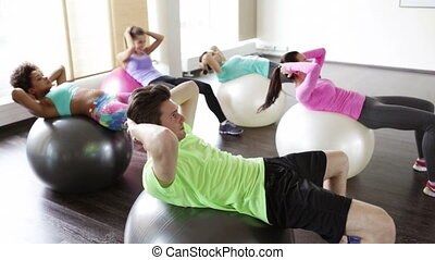 happy people flexing abdominal muscles on fitball - fitness,...