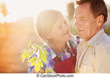 Senior couple in their garden - Senior couple enjoying a...