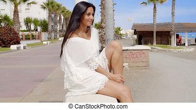Brunette Woman Sitting on Beach Promenade Wall - Portrait of...