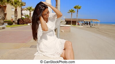 Brunette Woman Sitting on Beach Promenade Wall - Attractive...