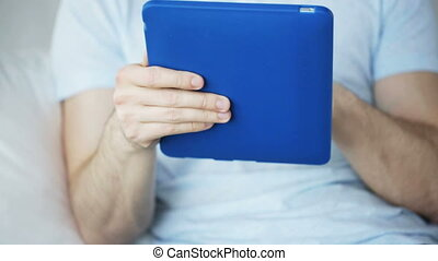 close up of man with tablet pc computer at home -...