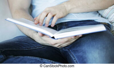 close up of man reading book at home