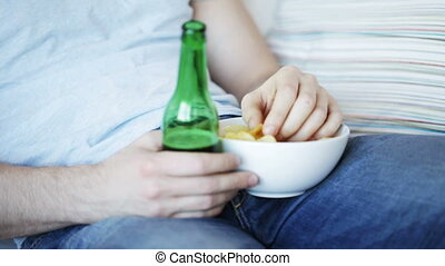 close up of man eating chips and drinking beer - food,...