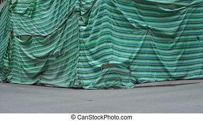 Building Covered for Restoration - Tilt up shot of a green...