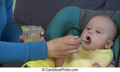 babysitter feed infant - Closeup of babysitter woman give...