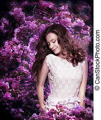 Pure Beauty. Dreamy Young Woman among Flowering Trees
