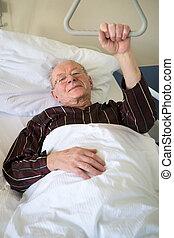 Frail senior man lying in a hospital bed on a ward...