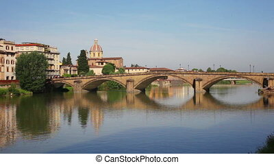 Florence, bridge through the river Arno is reflected in...