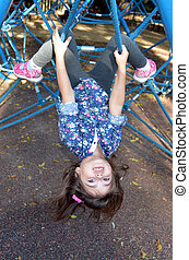 Little child paly on spider web bar in outdoor playground -...
