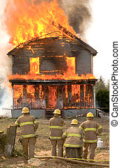 Firemen at a burning house - Some firemen stand in front od...