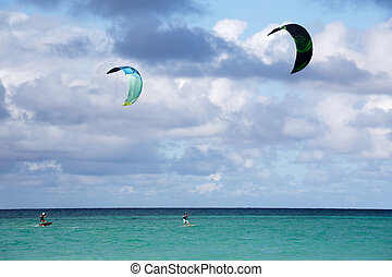 Kite surfing - Two people kite surfing at the beach
