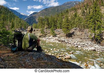 Backpacker on break - A male backpacker rests beside his...