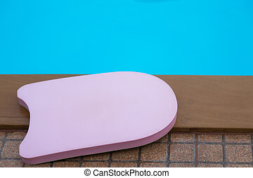 Pink boogie board in swimming pool