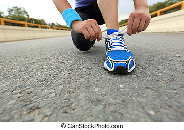 young woman runner tying shoelaces on city birdge road -...