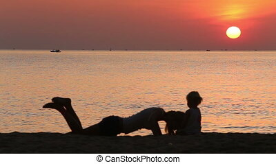 silhouette of mother and toddler doing exercises at sunrise
