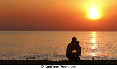 silhouettes of mother and daughter hugging on beach at sunrise