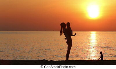 silhouette of mother playing with kid on beach at sunrise