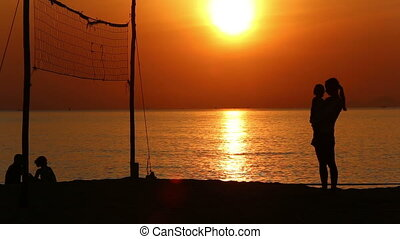silhouettes of mom and kid standing at volleyball net at...