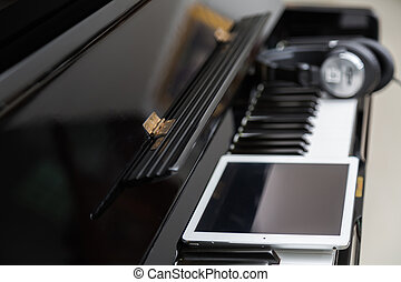 Tablet and head phones on Piano keys