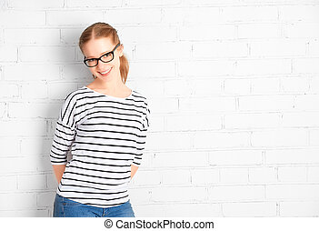 happy  girl student in glasses at a blank white brick wall