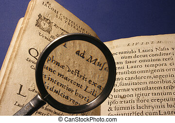 ancient book - detail of ancient book with magnifying glass