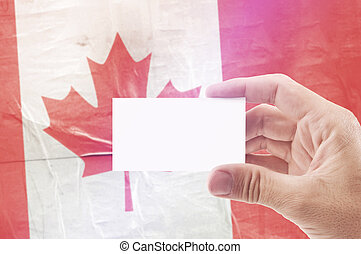 Man Holding Blank Business Card Against Canada National Flag...
