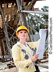 construction - A young female constructor at building of a...