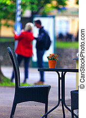 Couple standing at the summer cafe table with flowers