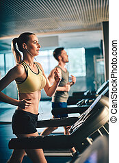 Fitness - Fit girl with earphones running on treadmill and...