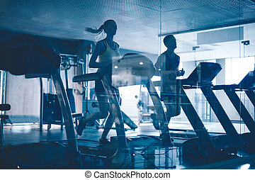 Treadmill workout - Active young people running on...