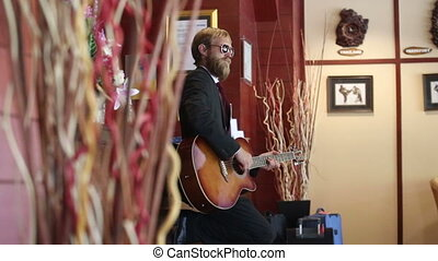 man in black plays guitar among curtains - man in black suit...
