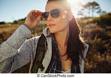 Beautiful young woman hiking on a summer day - Portrait...